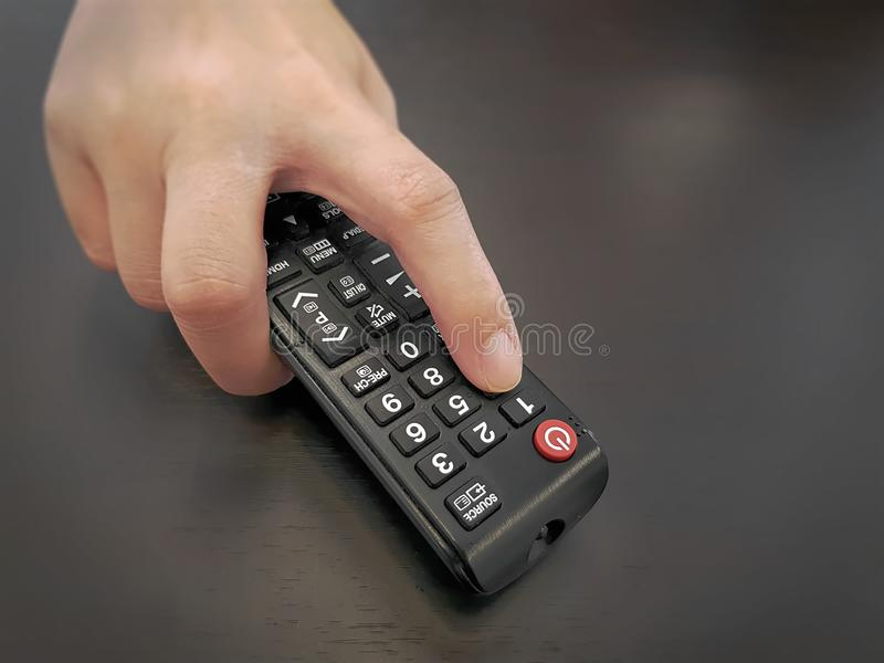 Ideia de ângulo alto da mão que guarda o controlador remoto imagem de stock