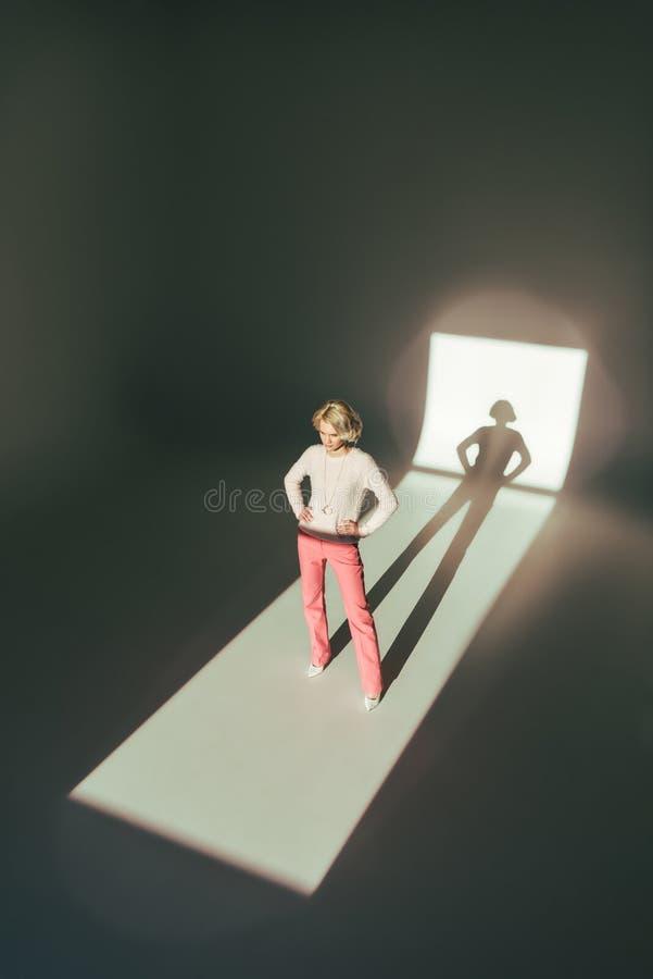 ideia de ângulo alto do modelo de forma fêmea novo na roupa cor-de-rosa que está com mãos na cintura fotografia de stock
