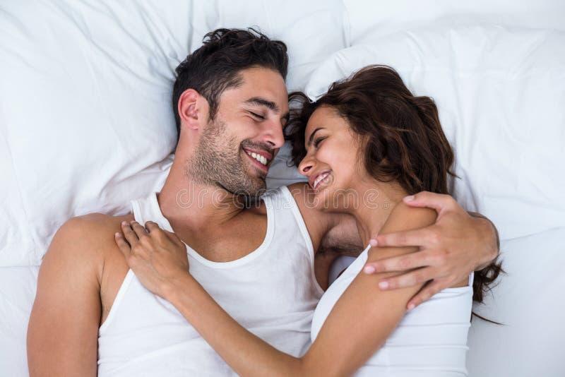 Ideia de ângulo alto dos pares felizes que relaxam na cama fotos de stock