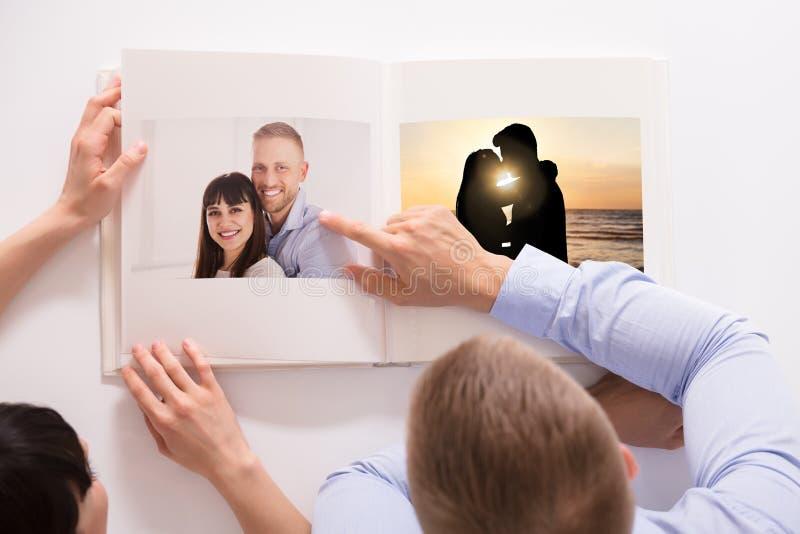 Ideia de ângulo alto de um par que olha seu álbum de fotografias fotografia de stock royalty free