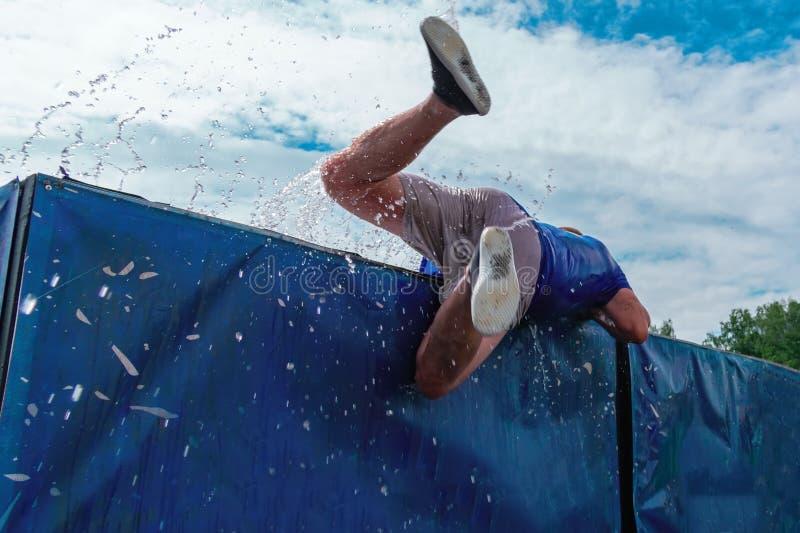 Ideia de baixo ângulo de sair do homem do obstáculo da água contra o céu durante uma raça extrema da lama Vista traseira fotos de stock