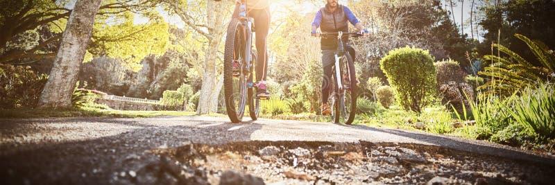 Ideia de baixo ?ngulo do ciclismo dos pares do motociclista na estrada do campo imagem de stock royalty free