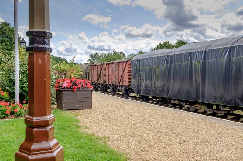 Ideia de camionetes cobertas antiquados da carga e do desembarque visto vagões de uma plataforma railway fotografia de stock royalty free