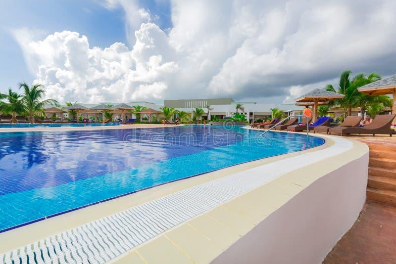 ideia de convite bonita da piscina acolhedor confortável com os povos que relaxam e que nadam no fundo imagem de stock