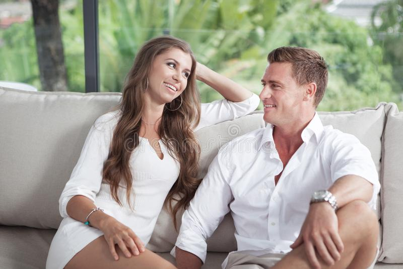 A ideia de pares novos agradáveis está sentando-se no sofá na casa de verão imagens de stock