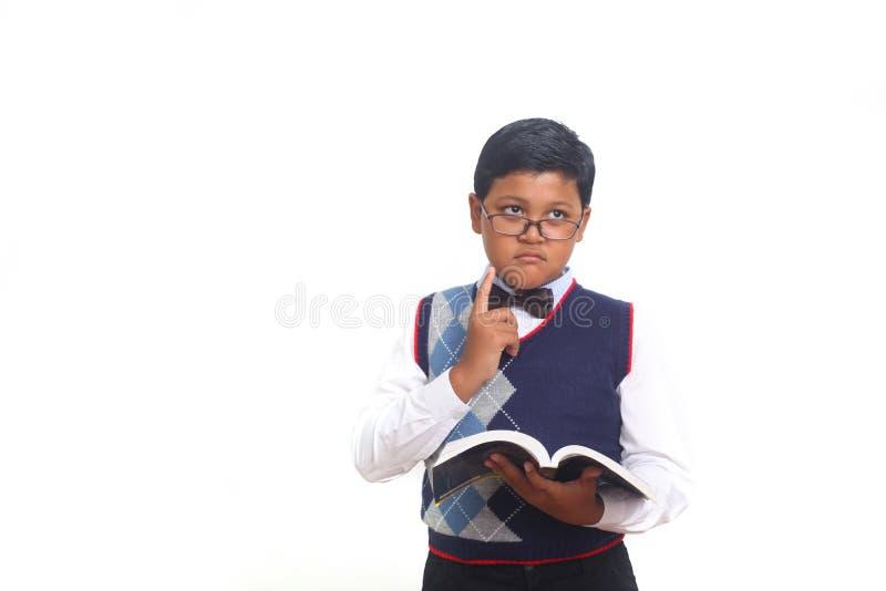 Ideia de pensamento da estudante bonito ao vestir vidros e ao guardar um livro, isolado no fundo branco fotografia de stock