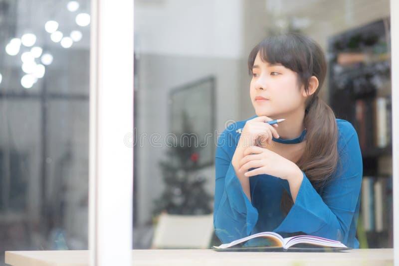 Ideia de pensamento de sorriso do escritor asiático novo bonito da mulher do retrato e escrita no caderno ou no diário com feliz, imagens de stock royalty free