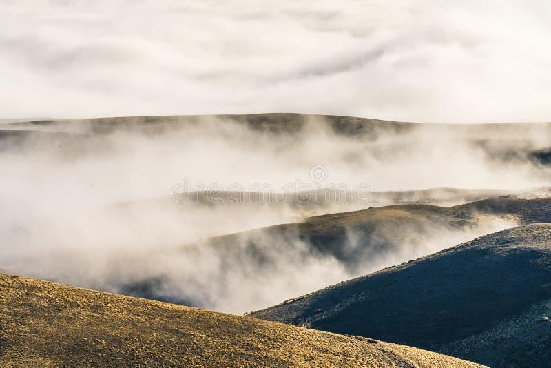 Ideia de surpresa de camadas da cordilheira com o mar da névoa e da nuvem acima do monte de vidro secado amarelo dourado no Patag foto de stock royalty free
