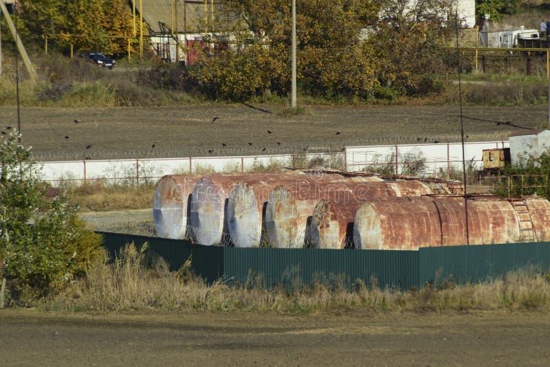 Ideia de uma base velha de lubrificantes combustíveis Tambores para armazenar a gasolina Um pagamento velho imagens de stock