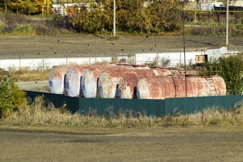 Ideia de uma base velha de lubrificantes combustíveis Tambores para armazenar a gasolina Um pagamento velho fotos de stock
