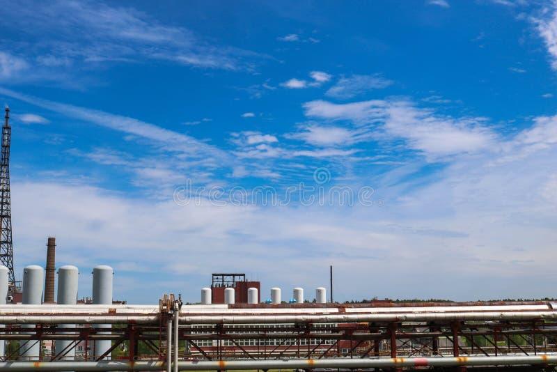 Ideia de uma passagem superior do encanamento com tubulações, colunas dos tanques contra um céu azul com nuvens em uma refinaria  fotografia de stock royalty free