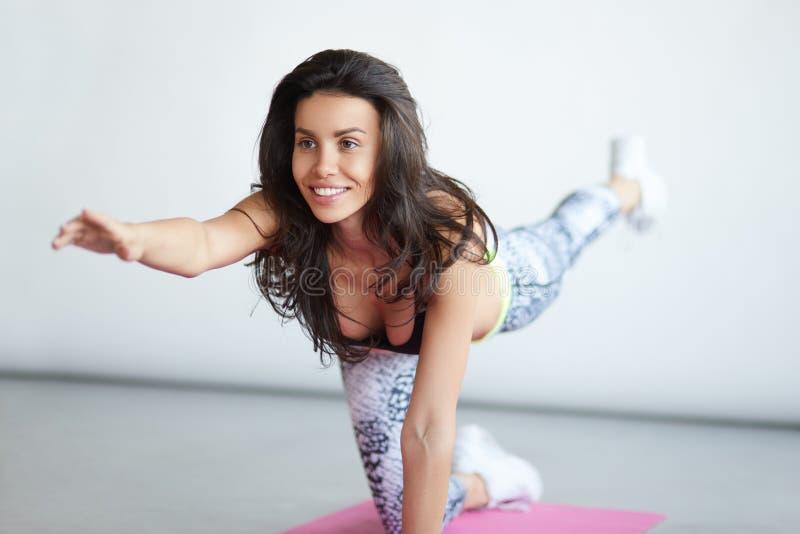 Ideia dianteira da ioga praticando de sorriso da jovem mulher bonita desportiva imagens de stock royalty free