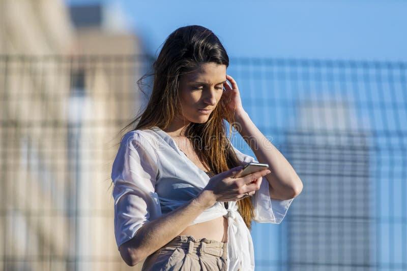 Ideia dianteira de um ar livre da posição da jovem mulher ao usar um telefone celular em um dia ensolarado imagem de stock royalty free