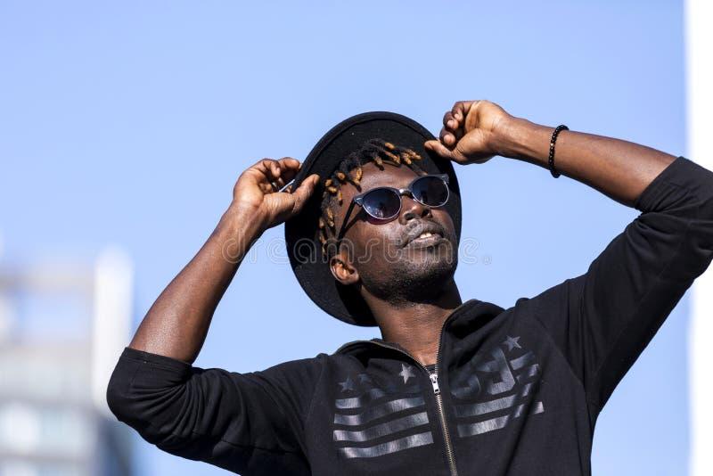 Ideia dianteira de um homem negro novo com óculos de sol e da posição do chapéu na rua contra o céu azul ao tocar no chapéu e na  imagens de stock