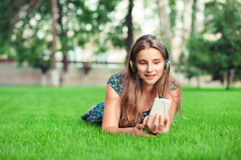 Ideia dianteira de uma música de escuta da menina da forma com fones de ouvido e o telefone esperto imagem de stock royalty free