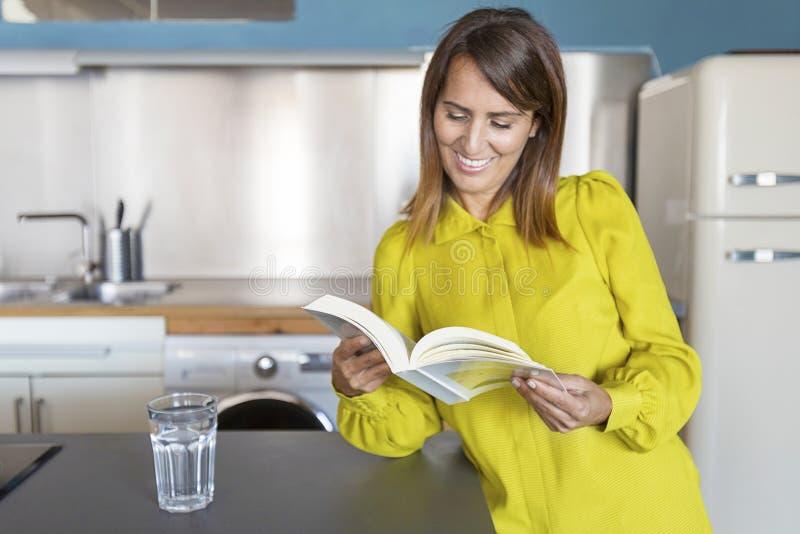 Ideia dianteira de uma posi??o bonita de sorriso da mulher na cozinha ao ler um livro fotos de stock royalty free
