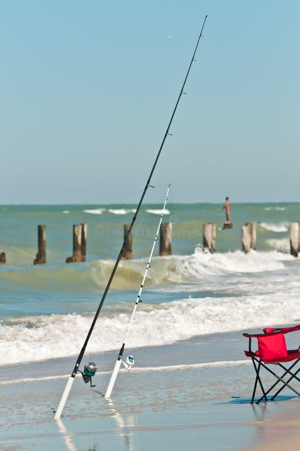 A ideia dianteira de uma zona tropical da ressaca da praia e dois surfam as varas de pesca nos suportes e em uma cadeira de praia fotografia de stock