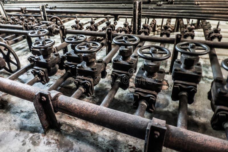Ideia dianteira do grupo de válvulas em umas tubulações oxidadas industriais velhas foto de stock royalty free