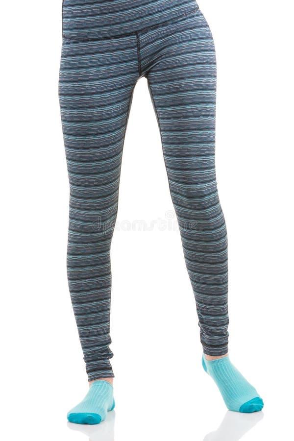 Ideia dianteira dos pés da mulher do ajuste em caneleiras listradas coloridas dos esportes e em peúgas azuis foto de stock