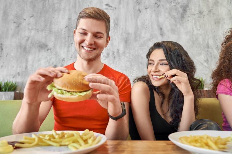 Ideia dianteira dos pares felizes que comem o fast food no café imagem de stock