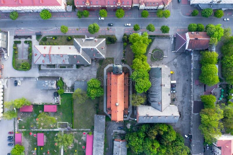 Ideia do bloco de cidade de cima de Telhados das casas e de uma igreja Católica no centro Entre as casas nos carros da movimentaç imagens de stock