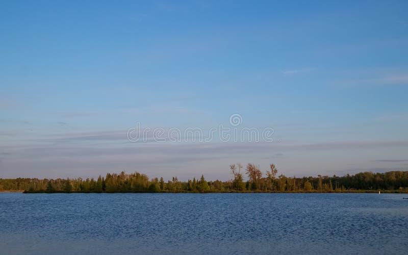 Ideia do Chippewa Flowage com as árvores decíduos e coníferas de Northwoods contra o céu do por do sol fotos de stock