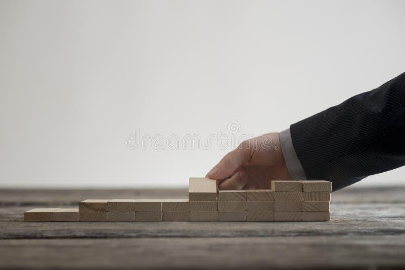 Ideia do close-up da mão masculina que constrói pouca escadaria fotografia de stock