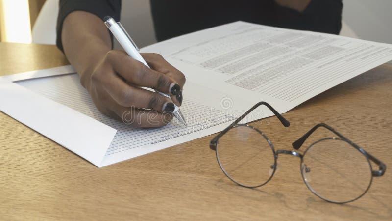 Ideia do close-up das mãos fêmeas africanas que enchem algo no formulário Menina na recepção Monóculos na tabela fotografia de stock