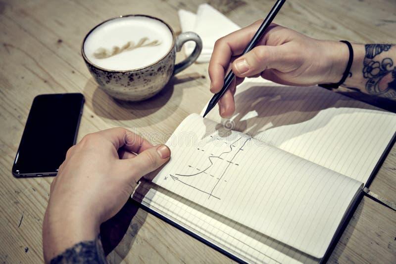 A ideia do close-up das mãos masculinas com livro de nota e o café tiram diagramms fotos de stock royalty free
