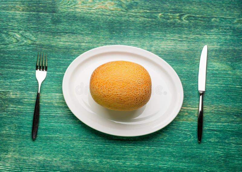 Ideia do close up de fatias frescas de um melão na madeira rústica da placa branca foto de stock
