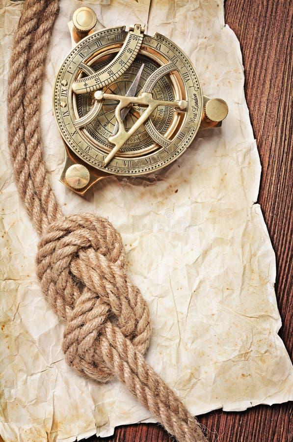 Ideia do close-up de um compasso do vintage e um nó da corda no papel manchado retro imagem de stock