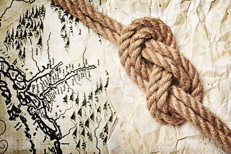 Ideia do close-up de um nó do mar da corda em um mapa retro velho fotografia de stock royalty free