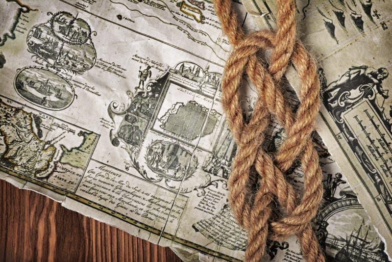 Ideia do close-up de um nó do mar da corda em um mapa retro velho imagem de stock