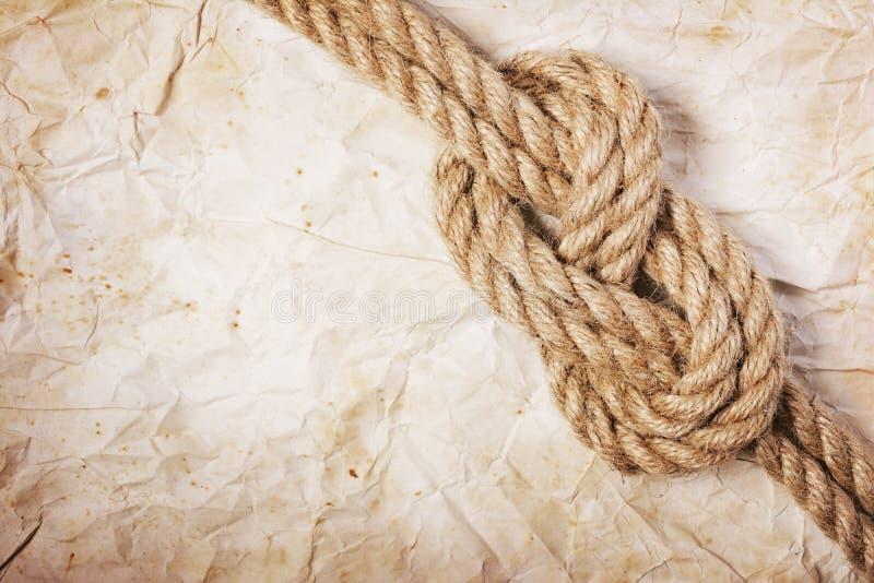 Ideia do close-up de um nó do mar da corda no papel retro foto de stock royalty free