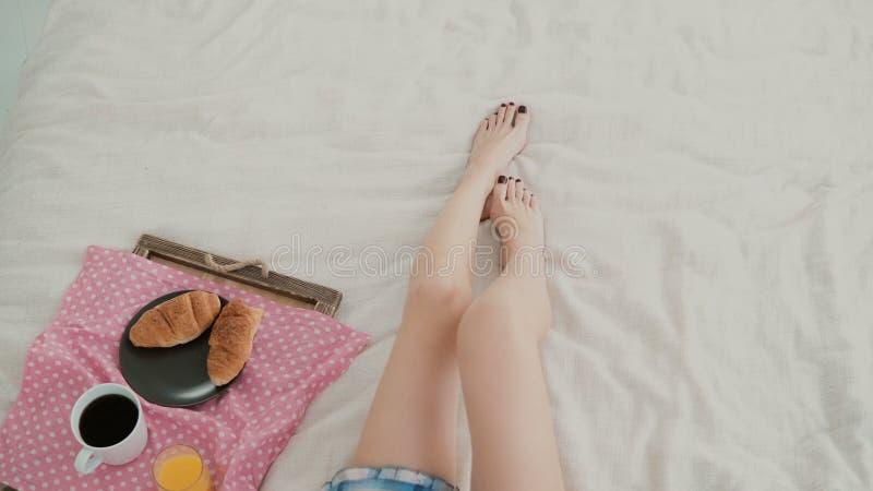 Ideia do close-up do pé da mulher s Moça que encontra-se na cama, comendo o café da manhã na sala de visitas foto de stock