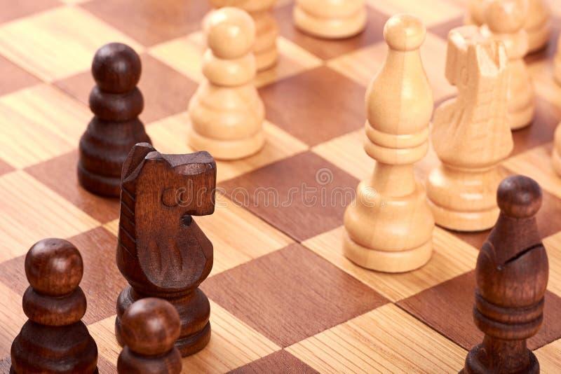 Ideia do close-up do jogo de xadrez com partes brancas e pretas do log no tabuleiro de xadrez marrom Luta com cavalo e penhores imagens de stock