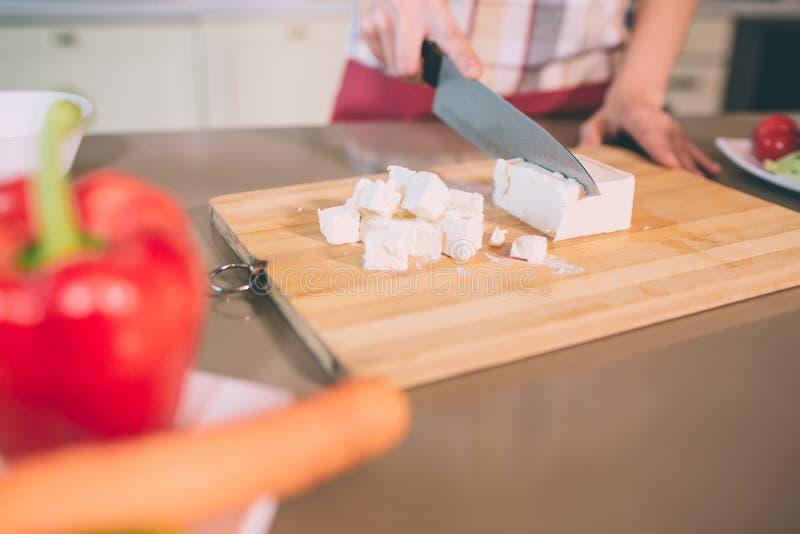 Ideia do corte das mãos da fêmea que cortam os chees brancos em partes na mesa Usa a faca Há cenoura e pimenta na placa foto de stock