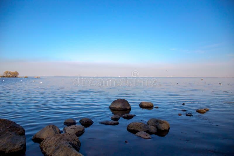Ideia do horizonte do Golfo da Finlândia com uma mansão em uma ilha pequena no museu de Peterhof Dia ensolarado da mola St Peters imagem de stock royalty free