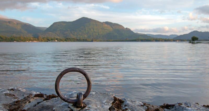 Ideia do por do sol do barco da doca do laço do anel de pedra acima da ANSR antiga de McCarthy das ruínas do castelo no lago Lean fotografia de stock royalty free