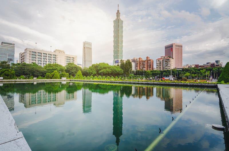 Ideia do por do sol da cidade de Taipei pelo beira-rio com arranha-céus e de reflexões bonitas em marcos lisos da água da torre d imagem de stock