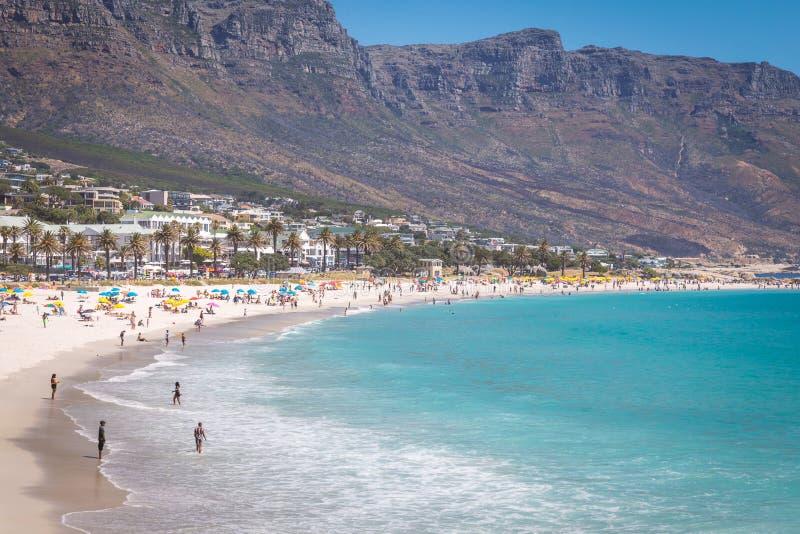 A ideia dos acampamentos late praia bonita com água e as montanhas de turquesa em Cape Town, África do Sul fotos de stock