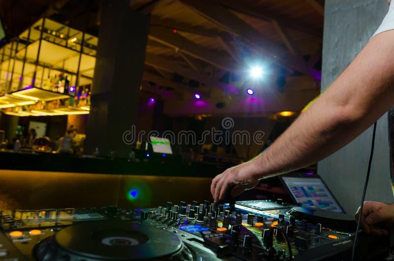 Ideia dos controles coloridos na plataforma com as mãos de uma música de mistura do DJ em um concerto imagem de stock