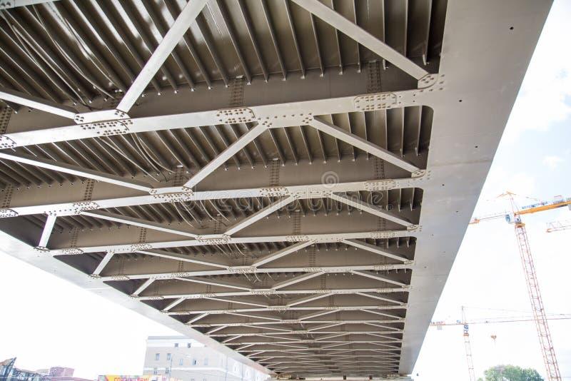Ideia dos feixes do metal da ponte através do rio de baixo no fundo de guindastes de construção foto de stock
