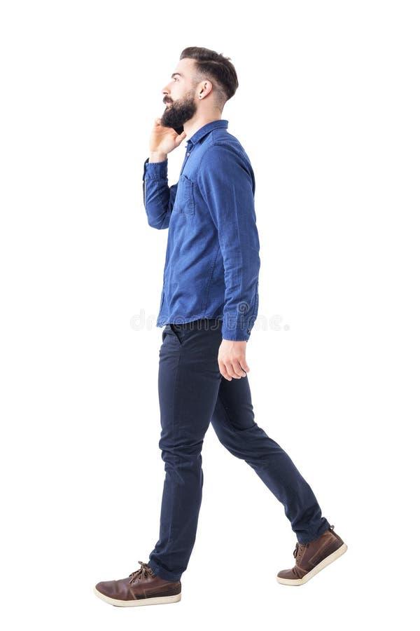 Ideia lateral da conversa ocupada segura do homem de negócios no telefone que anda e que olha acima imagem de stock royalty free