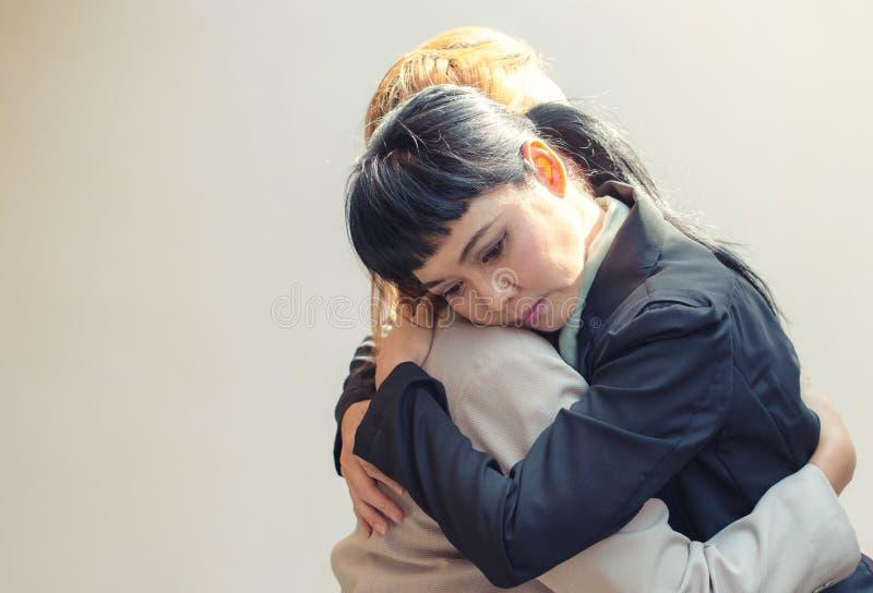 Ideia lateral de um abraço triste de dois amigos fotos de stock