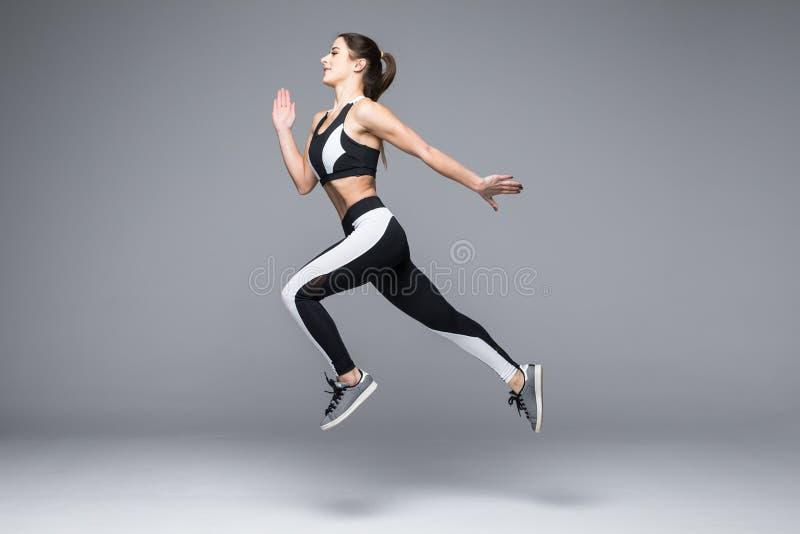 Ideia lateral de um salto desportivo da jovem mulher isolado no fundo cinzento foto de stock