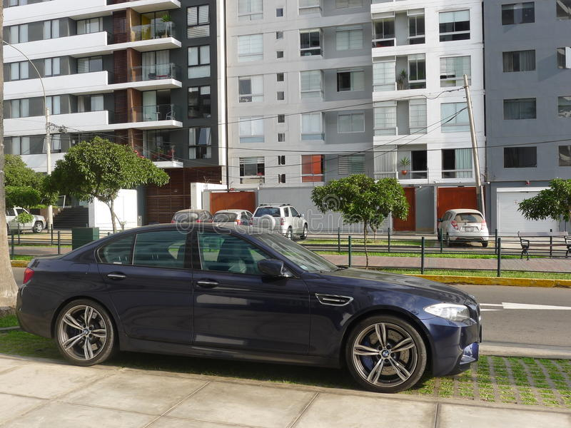 Ideia lateral de uma cor azul BMW M5 em Lima imagens de stock