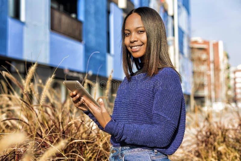Ideia lateral de uma posição afro-americano da menina, ao guardar a tabuleta em suas mãos e ao olhar a câmera imagens de stock royalty free