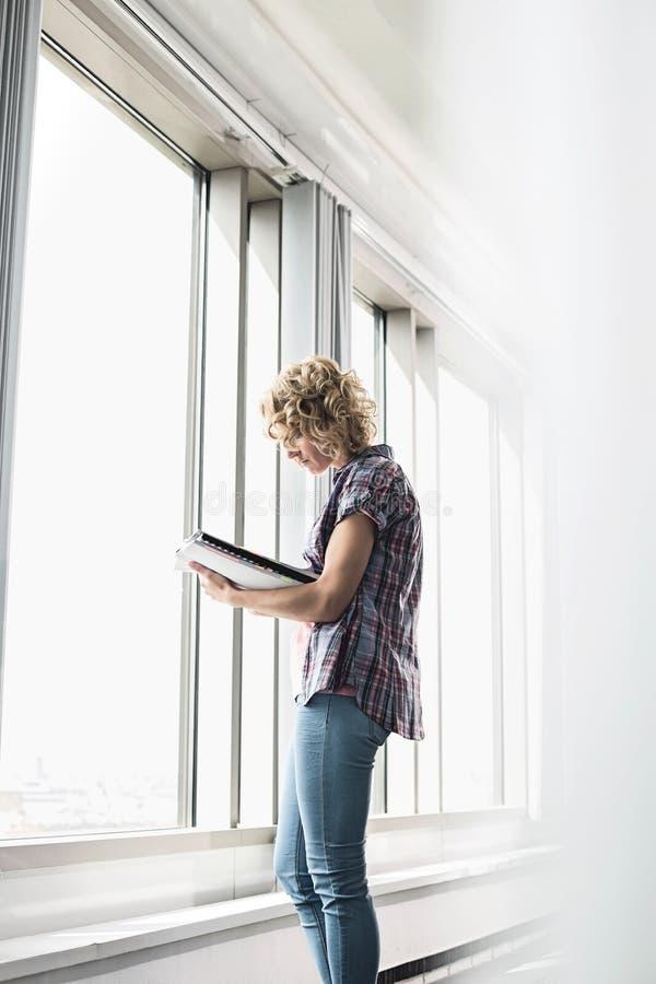 Ideia lateral do arquivo criativo da leitura da mulher de negócios pela janela no escritório imagem de stock