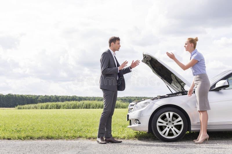 Ideia lateral do comprimento completo dos pares do negócio que discutem sobre carro quebrado no campo fotos de stock